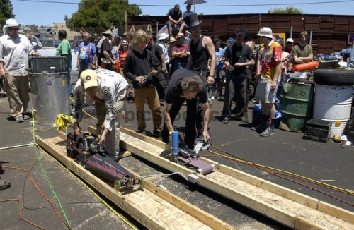 Contestants get ready at the start line with their power tool racing machines in the Power Tool Drag Races in San Francisco on June 13, 2004. For the third consecutive year, mechanic enthusiasts gathered in a San Francisco junkyard with their modified power tool machines to race side-by-side down a 75-foot wooden track. Most machines, attached to electrical cords, were based on common power tools such as circular saws, grinders, drills and belt sanders fitted with wheels. While most contestants competed for fun and for the underground type atmosphere, some hoped to win the $1,000 final grand prize.